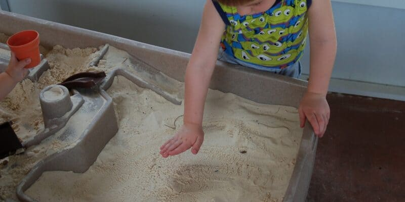 little boy playing in sand