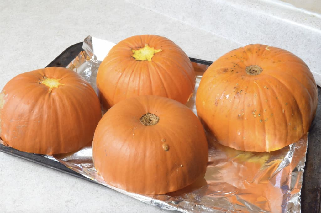 pumpkins cut in half on baking tray