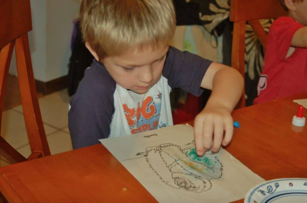 boy coloring with art sand