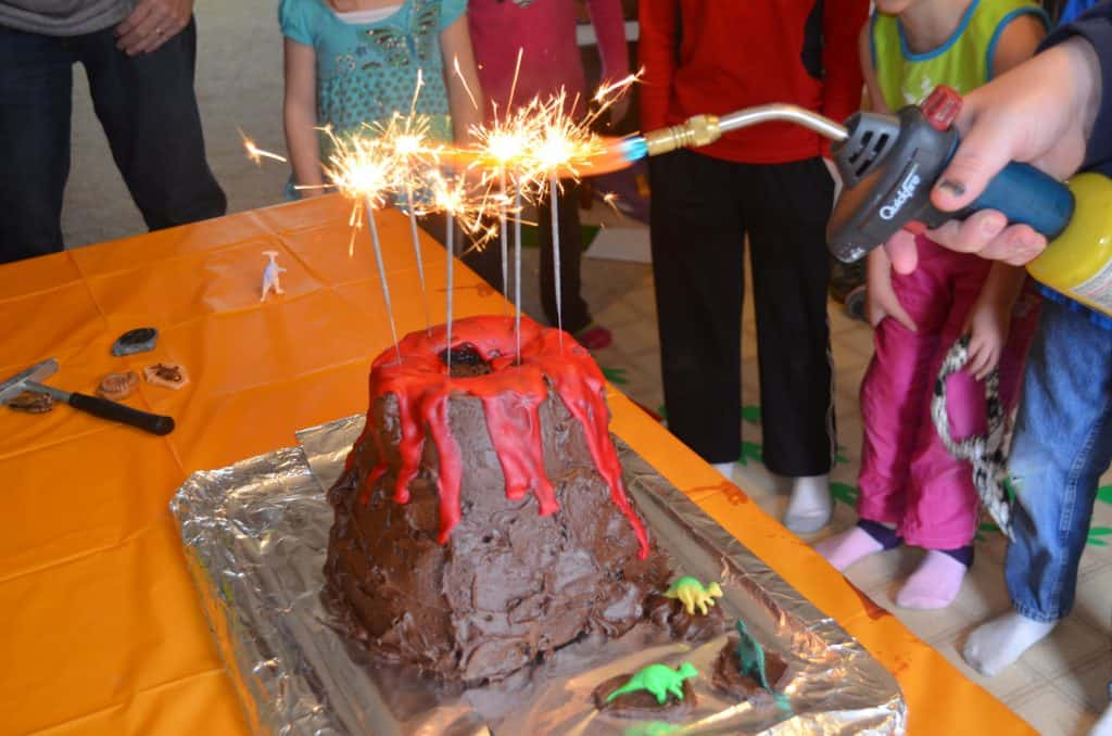 lighting sparklers on a dinosaur volcano cake tutorial