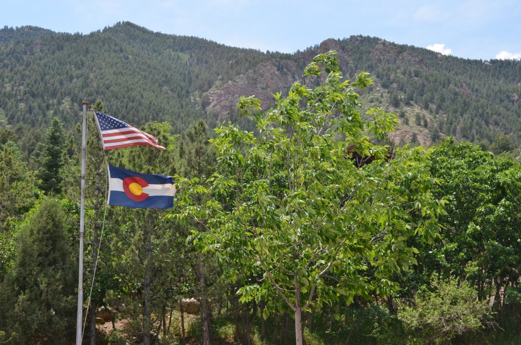 USA Flag and Colorado flag flying on mountain