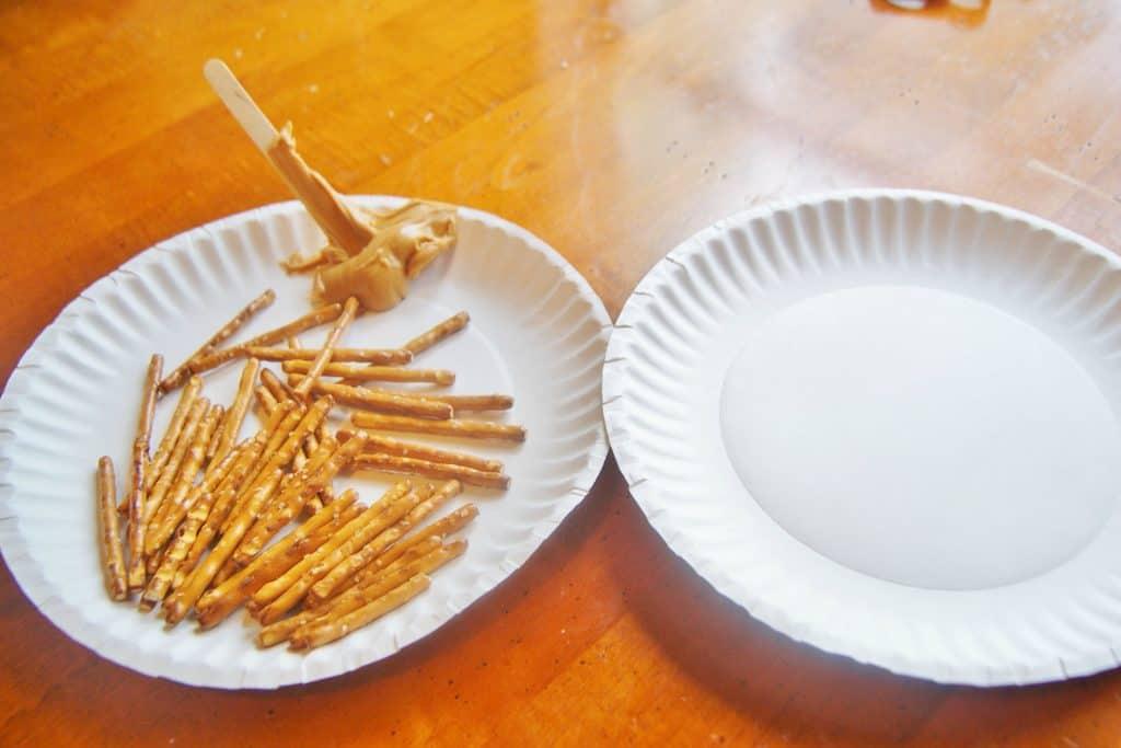plate of pretzel sticks with peanut butter