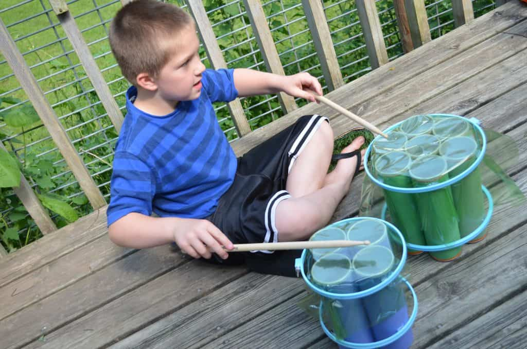 boy kid playing recycled drums