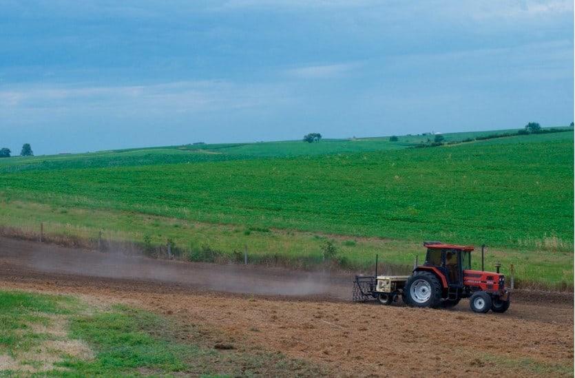 farming tractor plowing a field for a school butterfly garden
