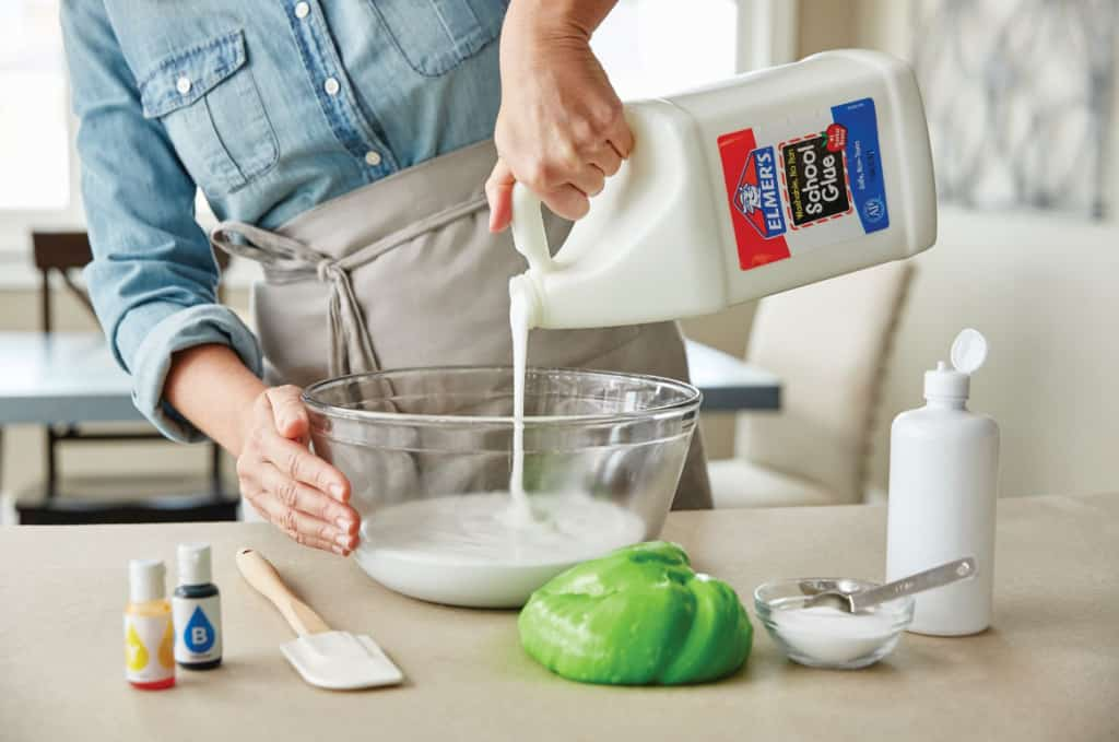 Pouring elmer's white school glue into a kitchen bowl as the first step in making slime recipe
