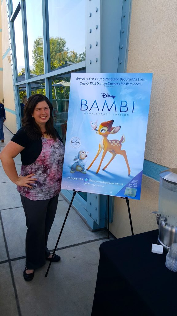 standing next to the Disney Bambi movie poster