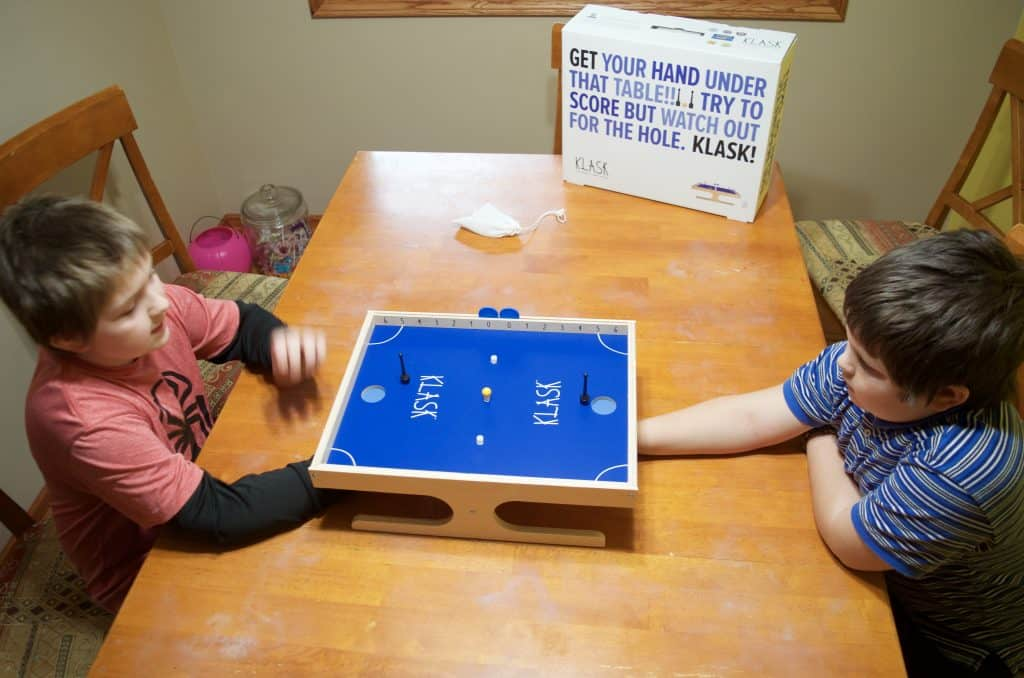 brothers playing Klask magnetic game