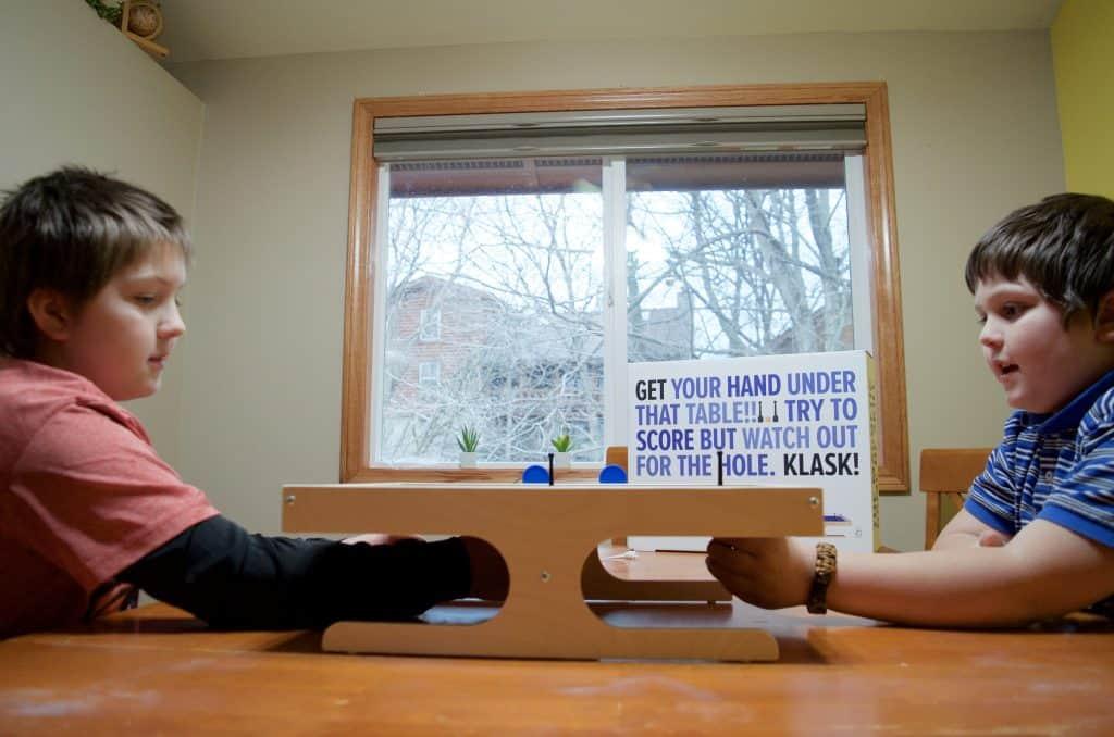 two boys playing Klask magnetic game