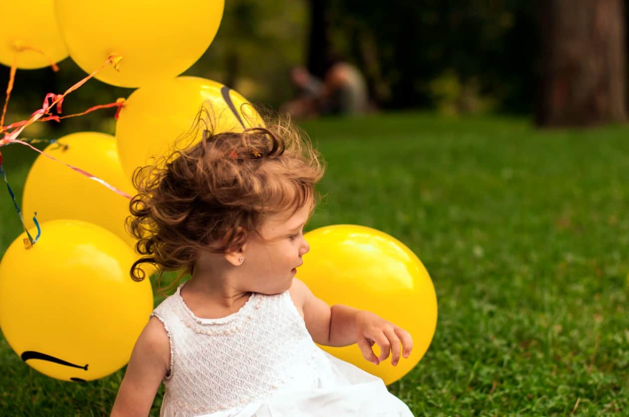 toddler girl with yellow balloons