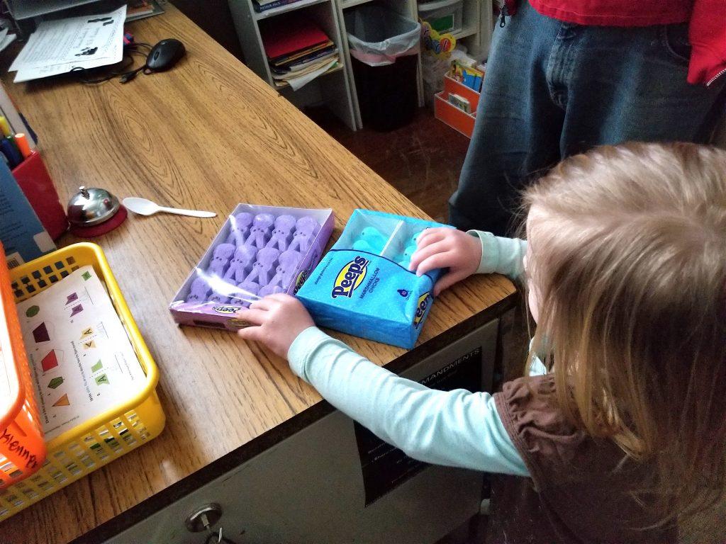 little girl putting PEEPS on desk