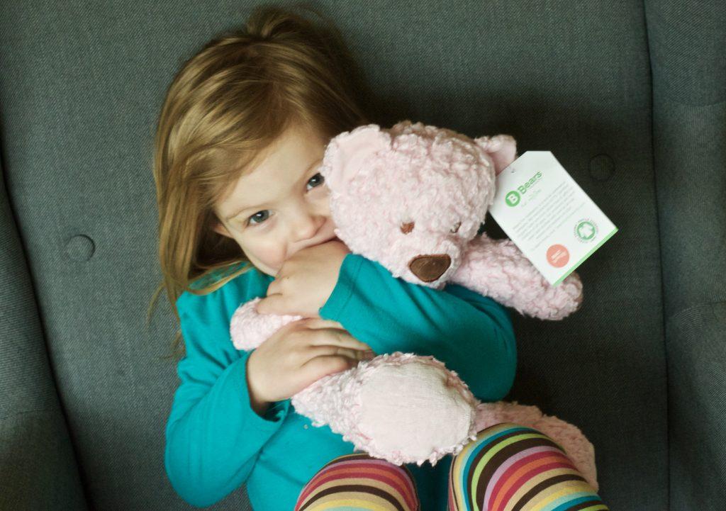 preschool girl hugging pink bear