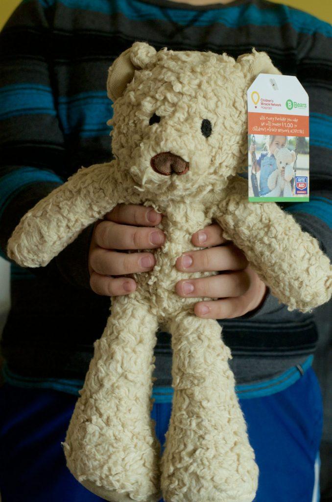 child's hands holding cream brown teddy bear plush