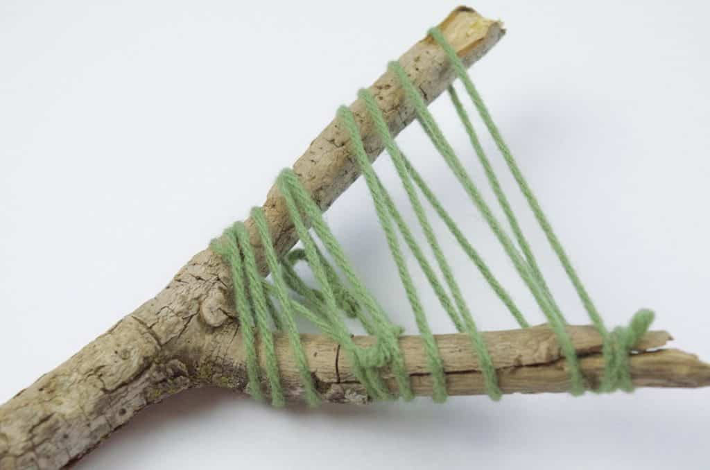 green yarn wrapped around stick camping craft
