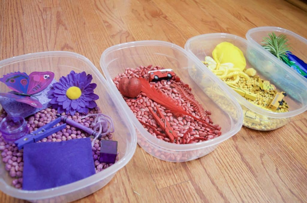 row of colored sensory bins for play