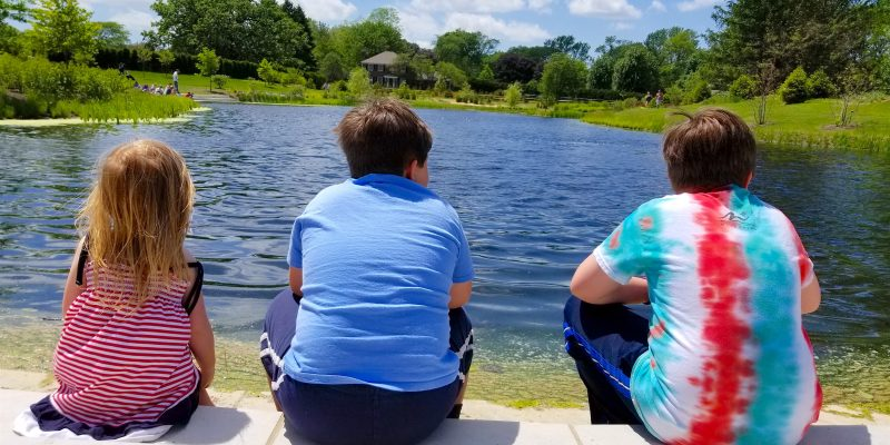 3 kids sitting in front of lake