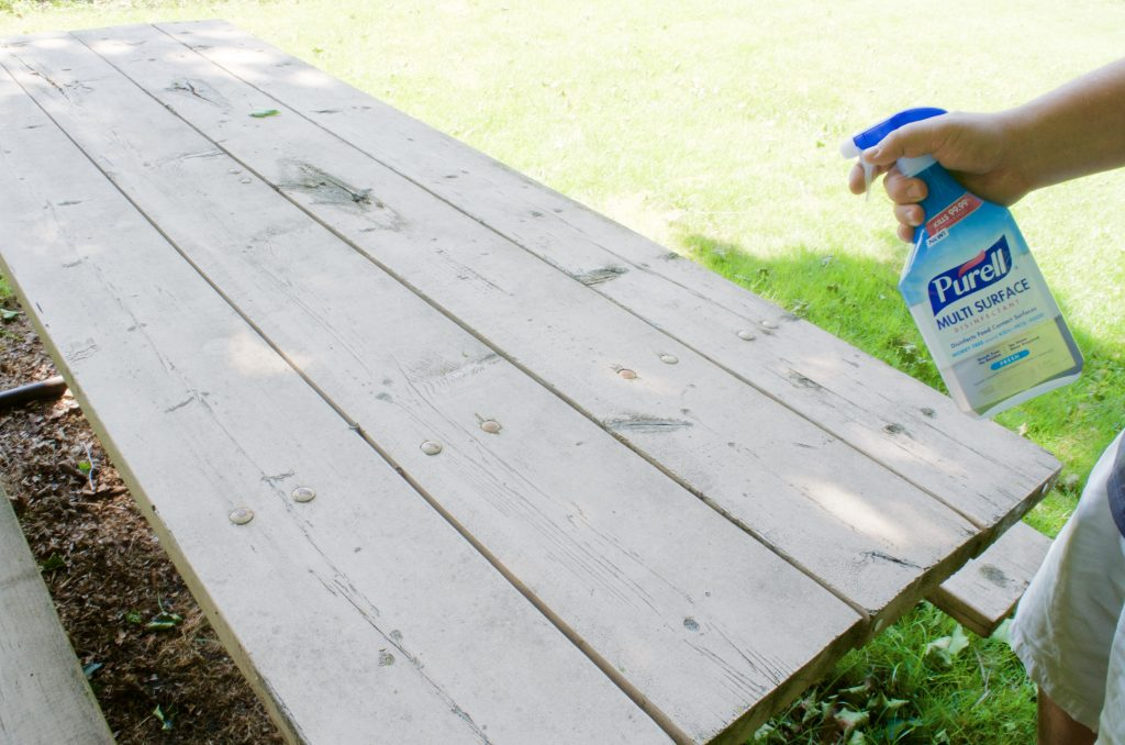 using PURELL Multi Surface Disinfectant on picnic table