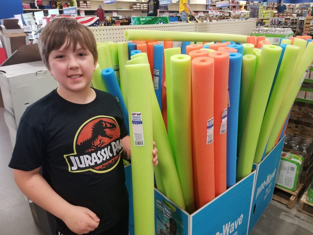 boy standing next to pool noodles at Theisen's