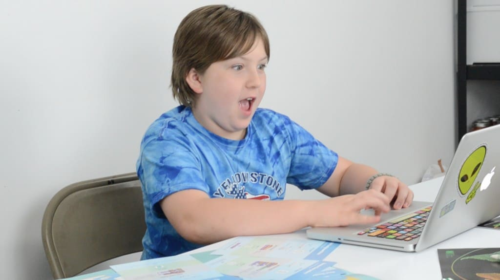 teen boy coding at computer surprised