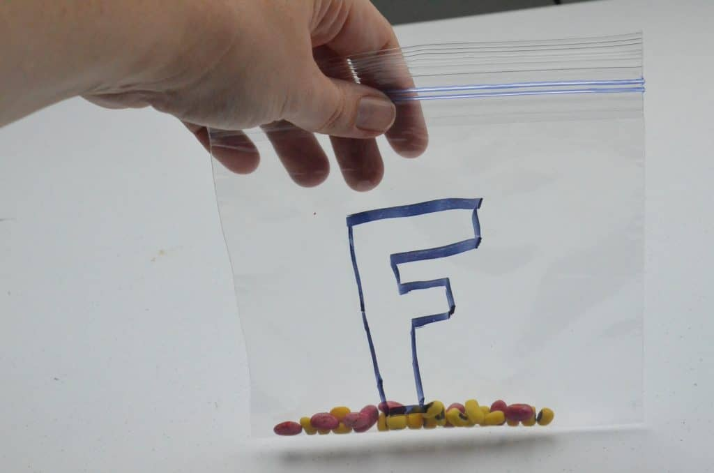 bag with letter F and colored beans for fire safety
