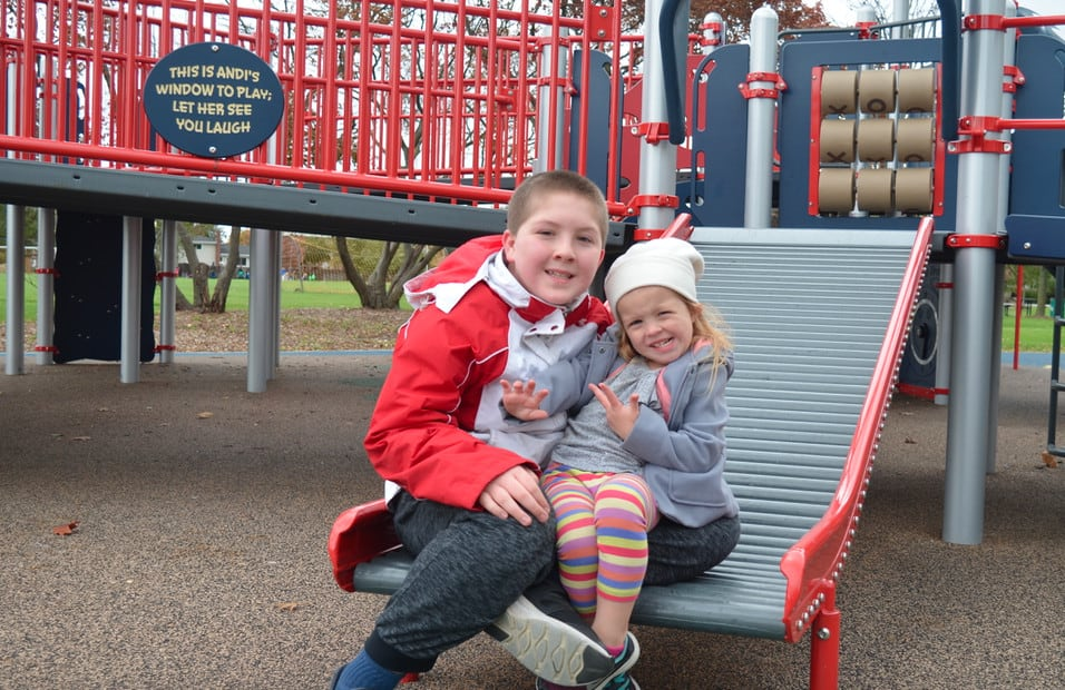 brother and sister at playground on roller slide