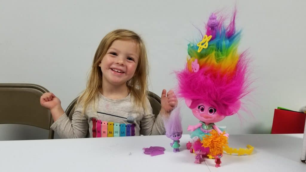 girl playing with DreamWorks Trolls toys