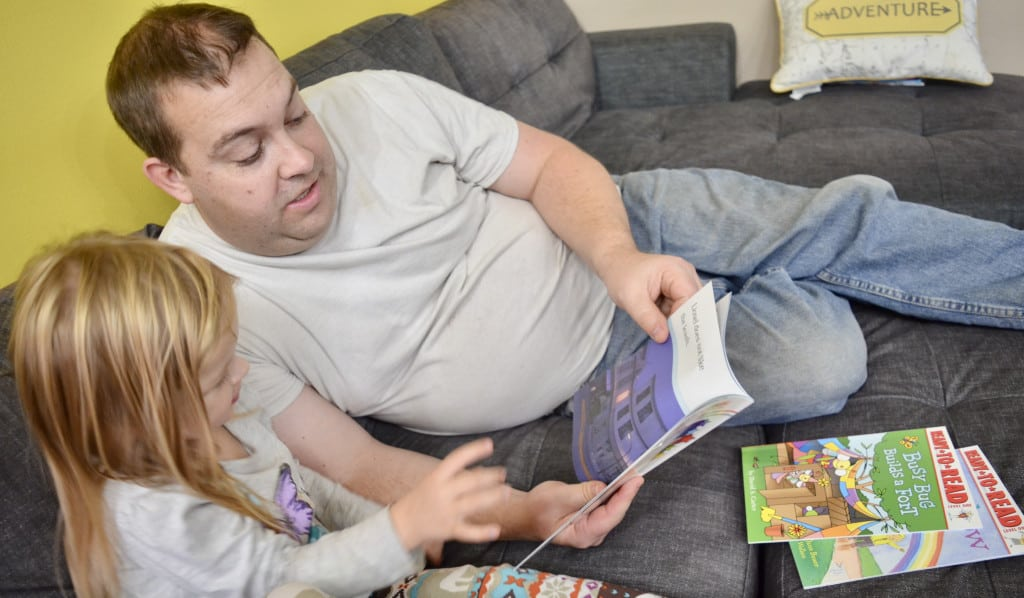 preschool girl reading books with dad