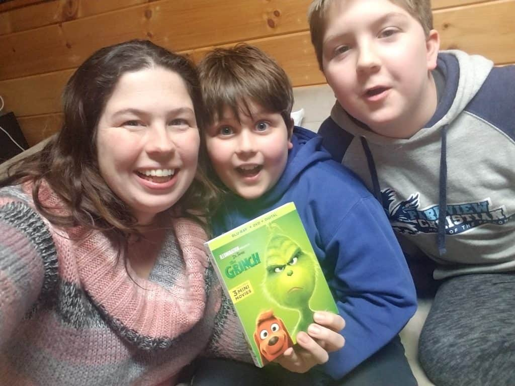mom with two boys family holding The Grinch movie