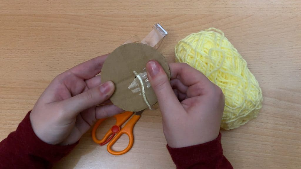 taping yellow yarn on cardboard circle