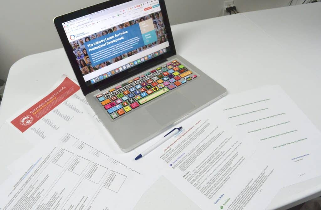 laptop with professional development handouts