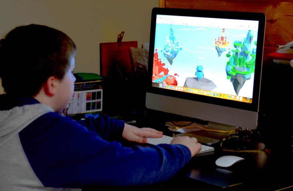 boy sitting at computer playing game