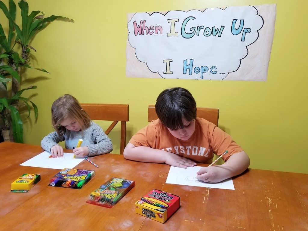 two kids drawing with art supplies