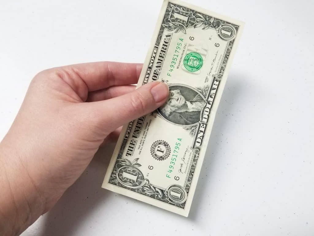 hand holding crisp new dollar bill