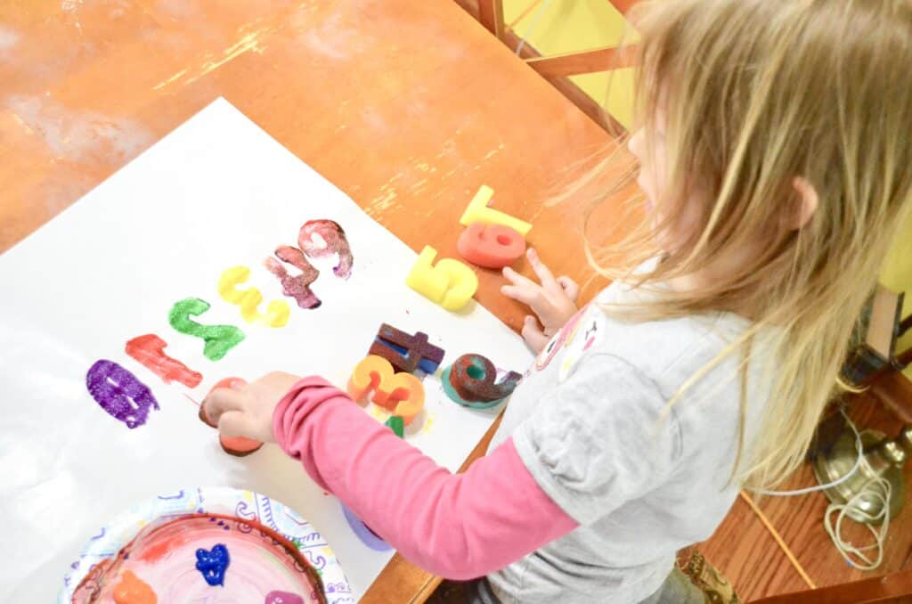 girl doing art letters and numbers