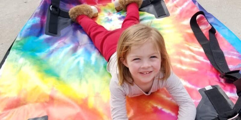 girl on tie dye car top carrier