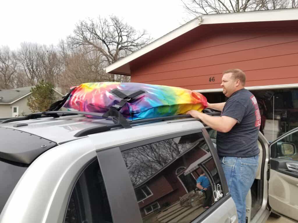man installing car top carrier