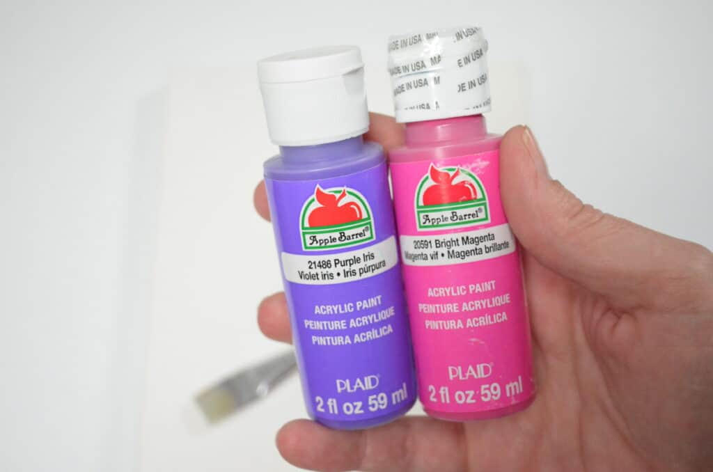 pink and purple acrylic paint bottles