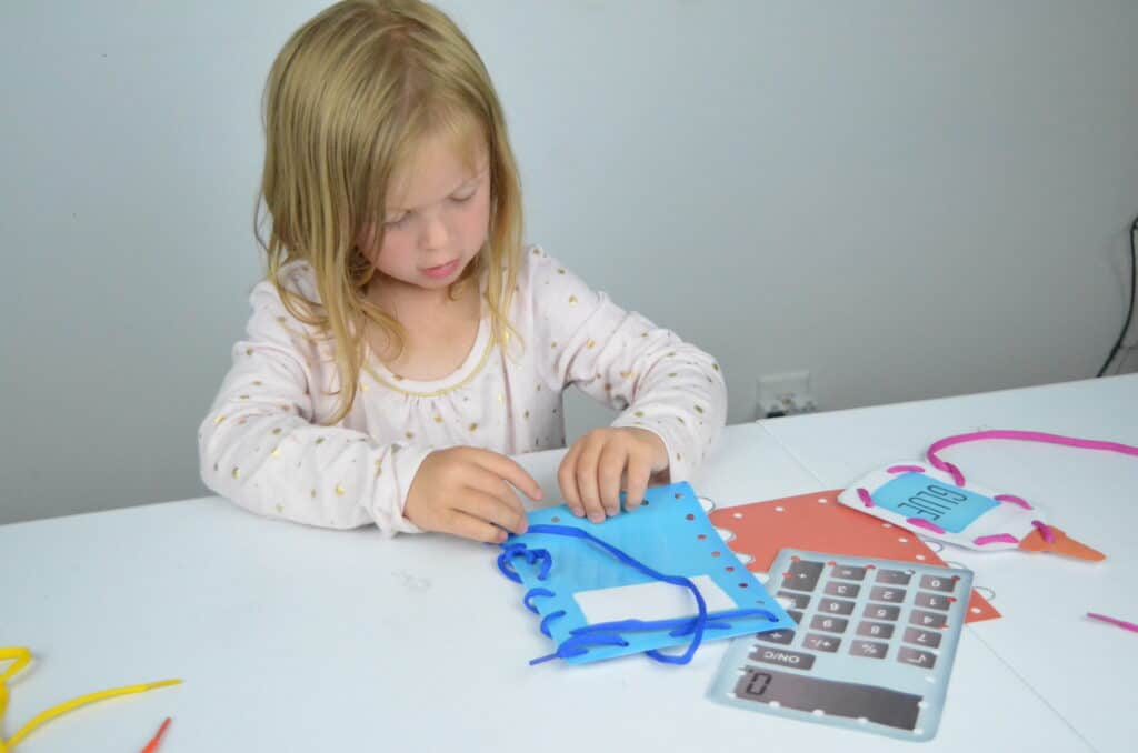 preschool girl lacing cards activity