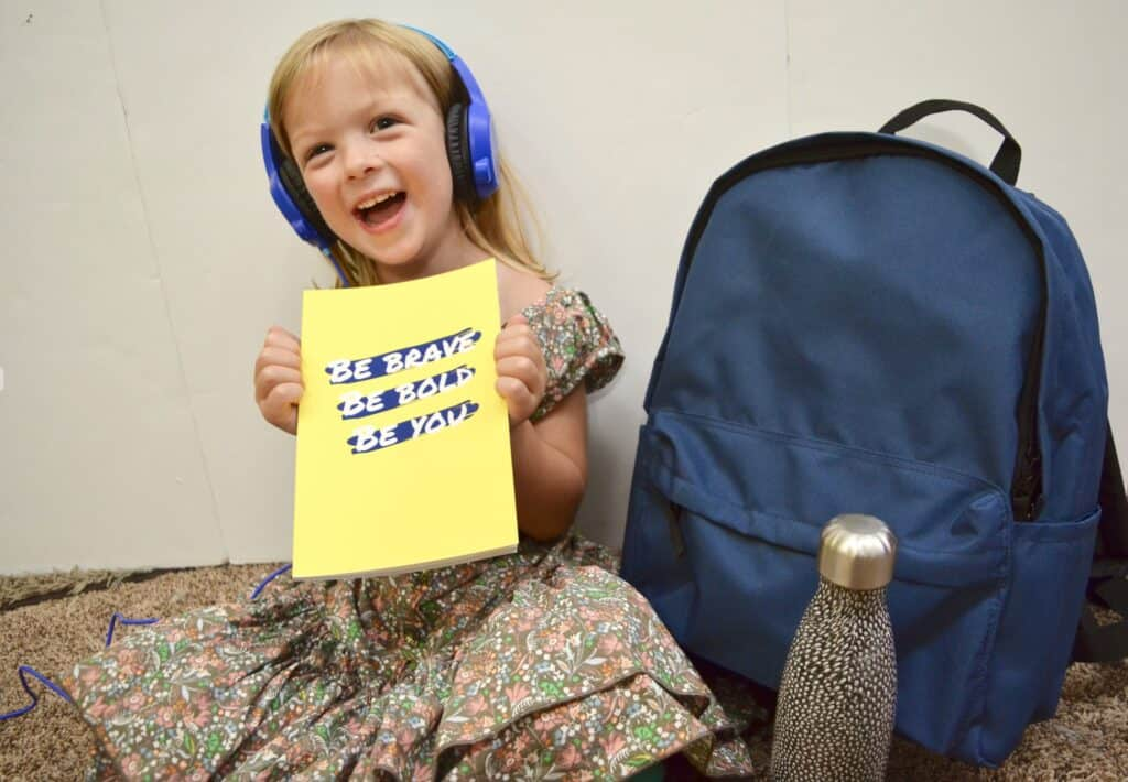 preschool girl with headphones school supplies