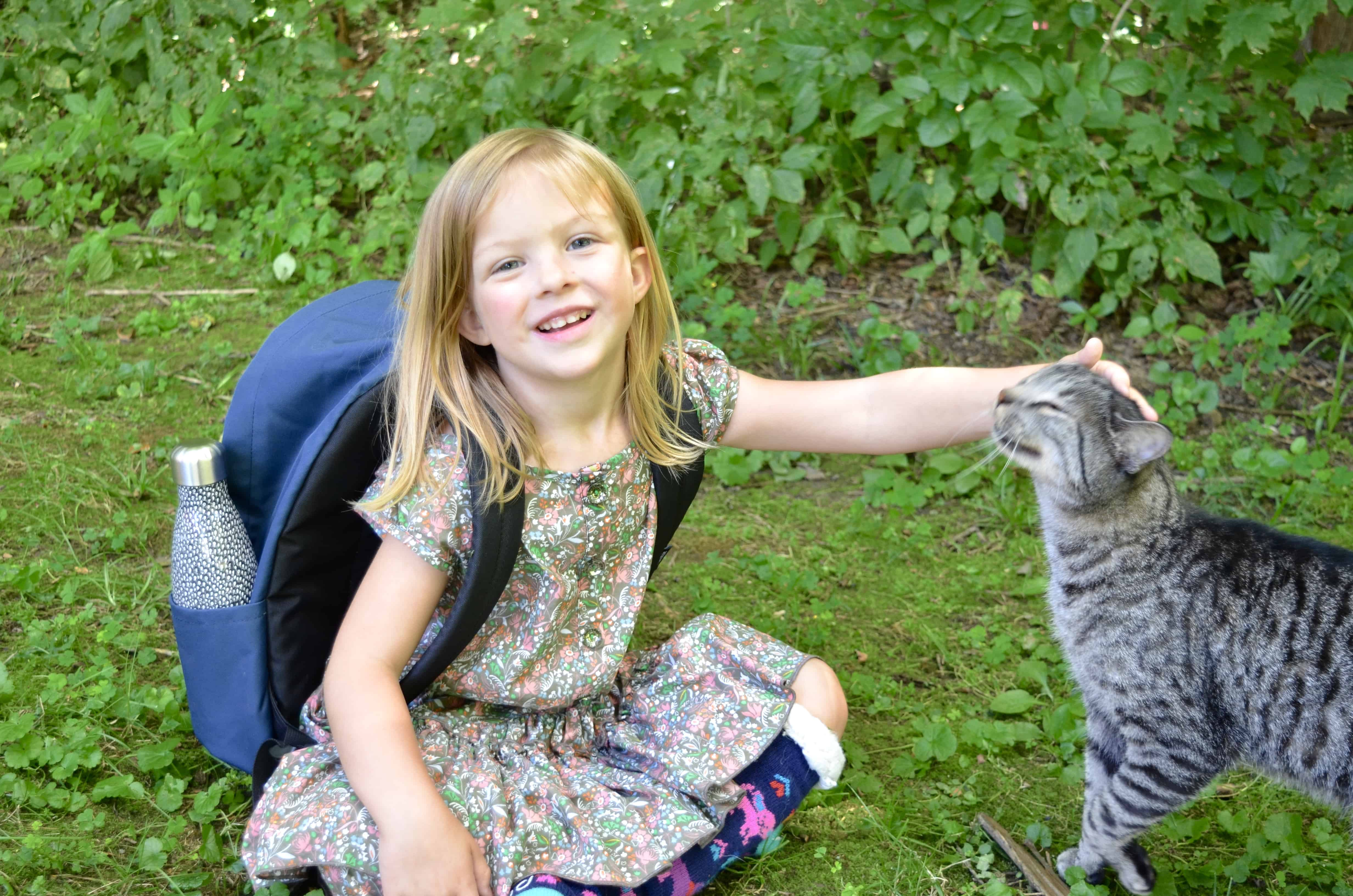 preschool girl wearing backpack petting cat