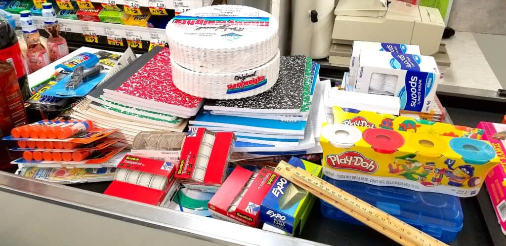 school supplies on grocery belt checkout