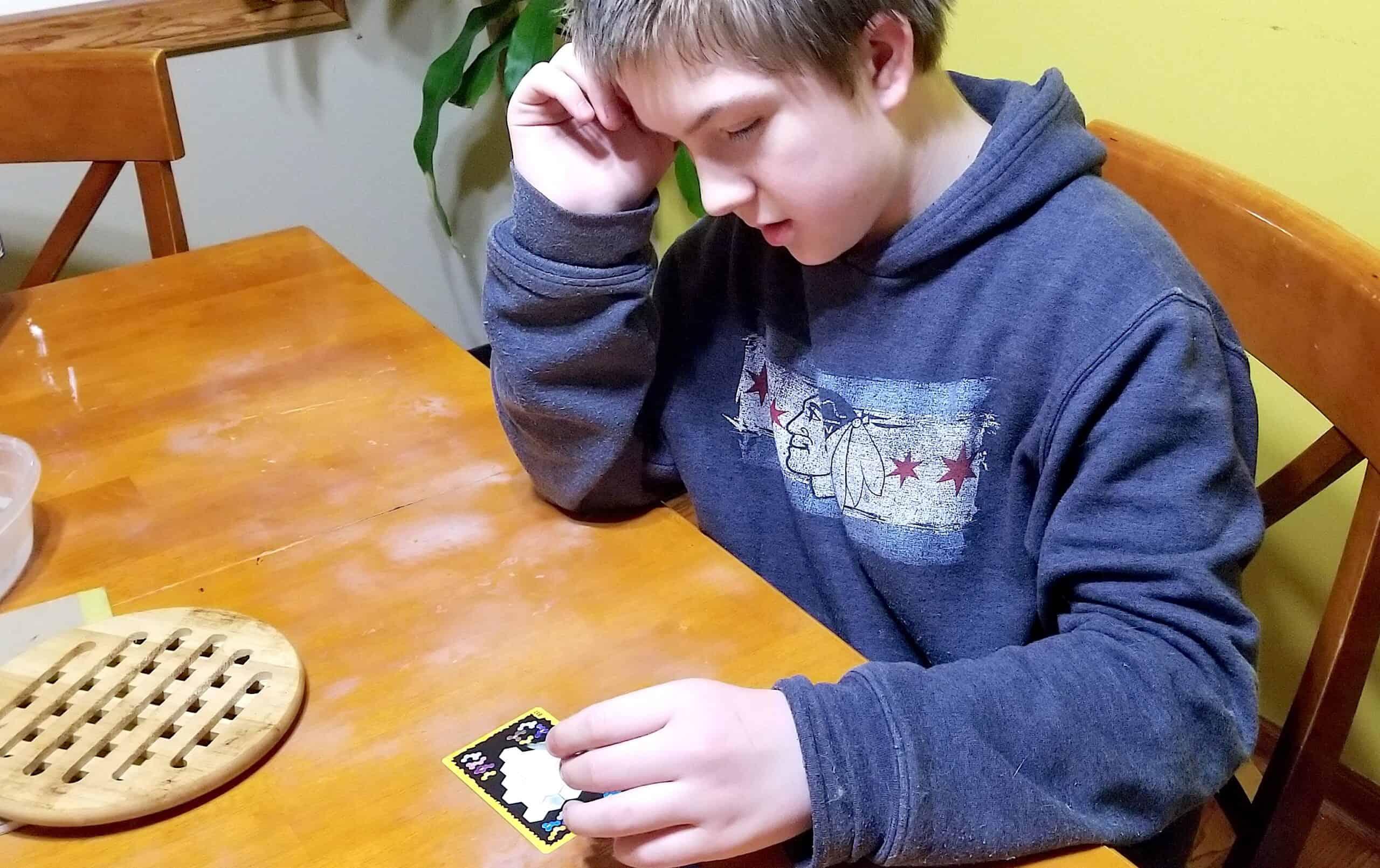 teen boy playing math game Ubongo Extreme