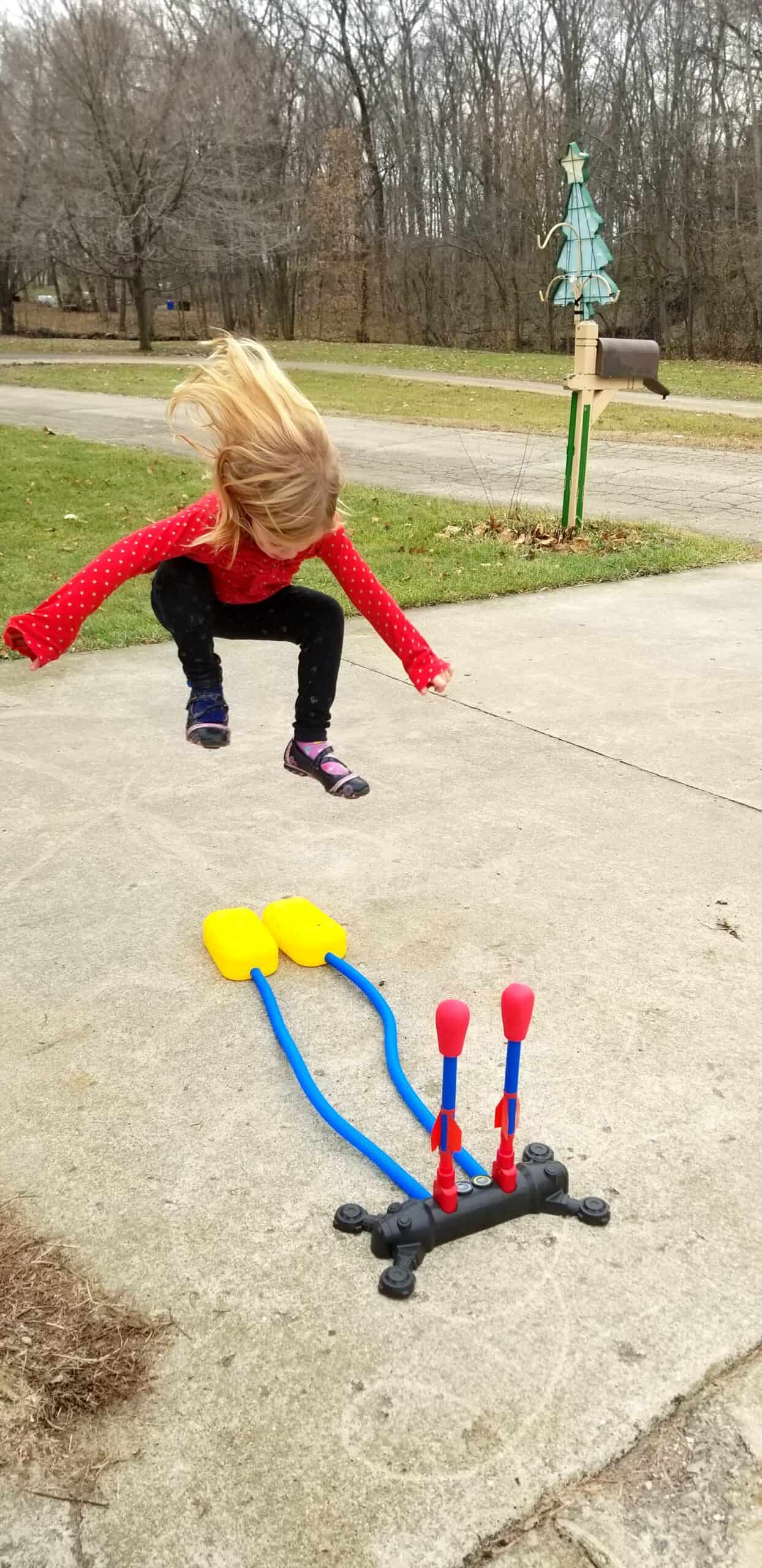 girl jumping on stomp rockets toy