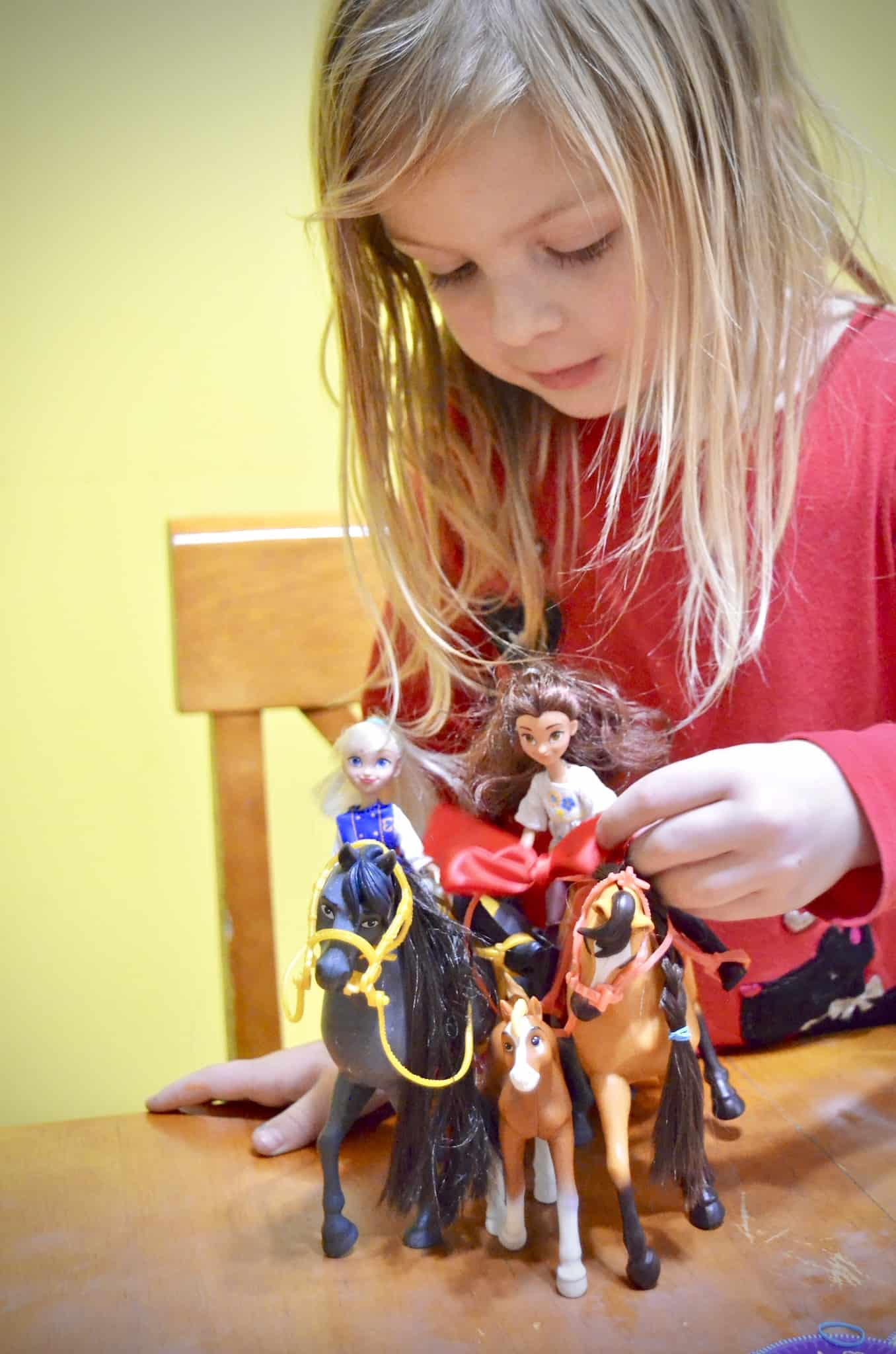 girl playing with Spirit horses toys