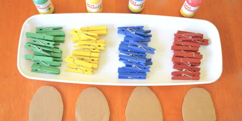 tray of colorful clothespins and paint