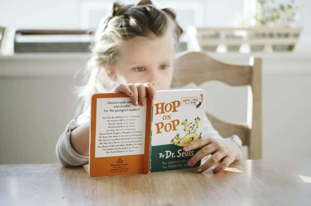 girl reading Dr Seuss book