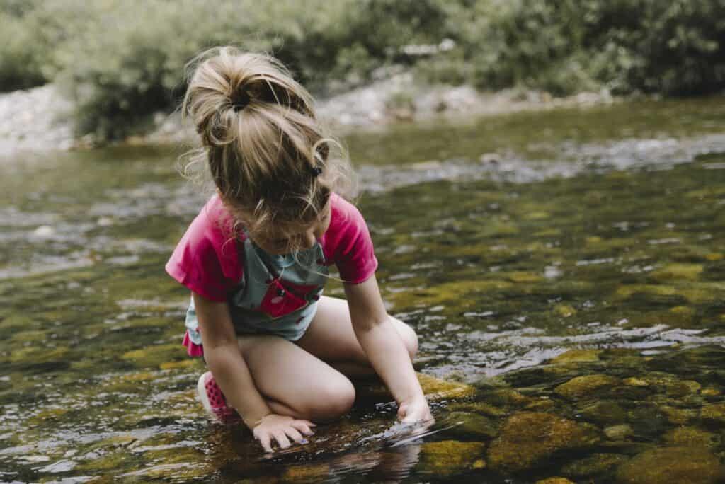 girl playing in lake water