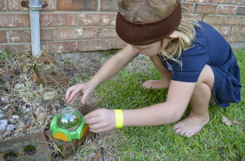girl outside catching bug habitat