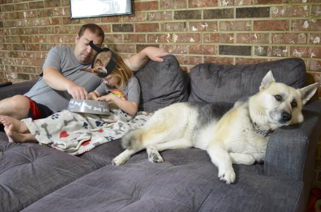 dad and daughter with dog watching tv