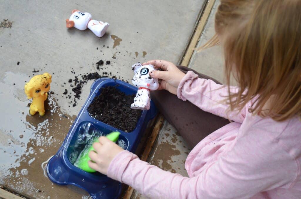 preschool girl washing dog sensory bin