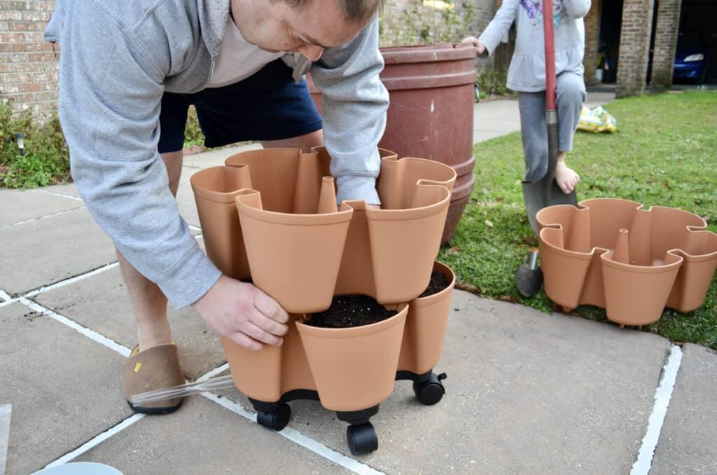 man pressing together GreenStalk Vertical Garden pieces